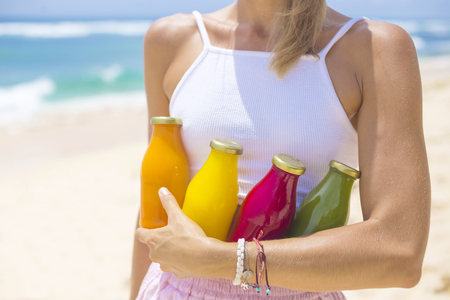 Young woman with Organic cold-pressed raw vegetable juice