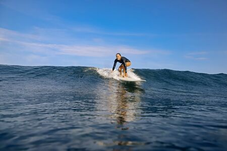 Female surfer on a blue wave at sunny day
