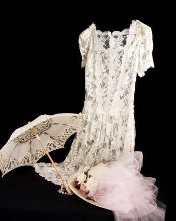 Vintage lace dress with parasol and old fashioned hat with netting and roses.