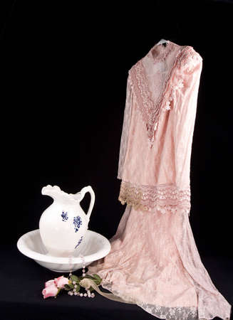 yesteryear: Vintage Pink Lace dress and old fashioned wash basin and pitcher from yesteryear Stock Photo