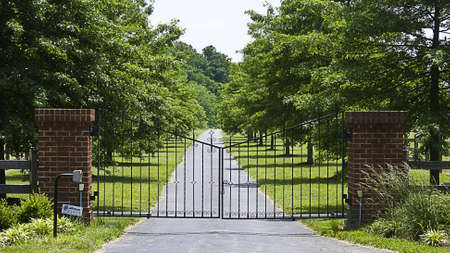 Iron gates open and close to estate on a treelined road. Imagens