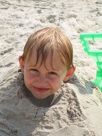 Childs head sticking out of sand at beach for fun photo