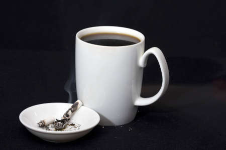 Cigarette bud burning in ashtray by cup of coffee photo