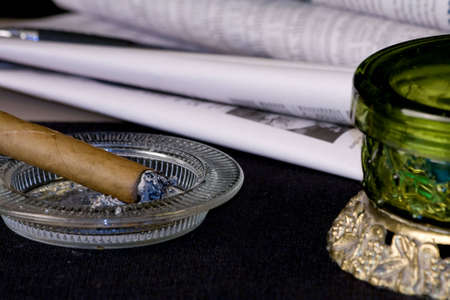 Cigar Alongside Newspapers