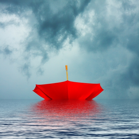 Upside down bright red umbrella floating on water background in stormy weather Stock Photo