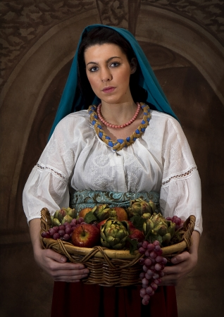 bushel: Young woman carrying basket of fruit dressed and in setting similar to an old world painting