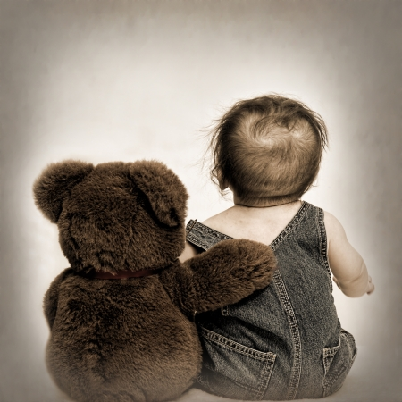 Small baby boy and his best friend, teddy bear sitting with their backs to us on brown gradient background