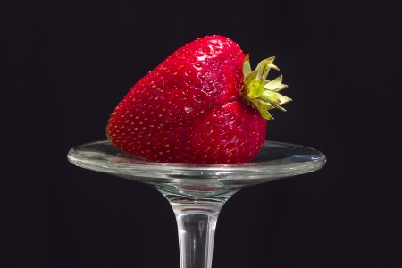 Serving one large red strawberry on upside down base of glass