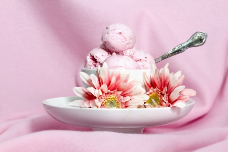 Strawberry icecream surrounding by strawberry gerber flowers against pink background