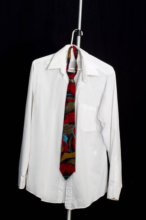 White man s dress shirt and tie hanging on hanger with black backround photo