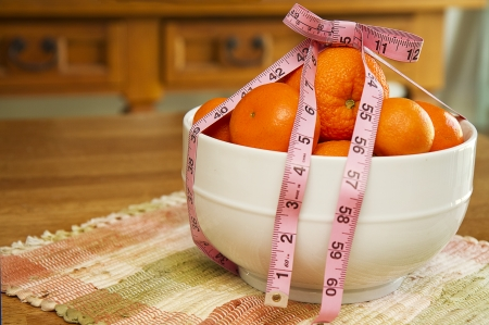 Bowl of oranges with tape measure surrounding it as cocept for losing weight