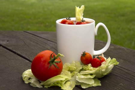 Tomato soup cocktail concept with small cherry tomatoes in drink with lettuce