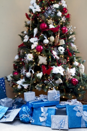 Christmas tree in home with blue silver presents beneath it Imagens