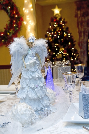 Beautiful and elegant table setting with lighted angels for Christmas Eve Dinner