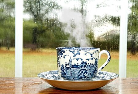 Antique cup and saucer with coffee on early rainy morning next to window pane Imagens