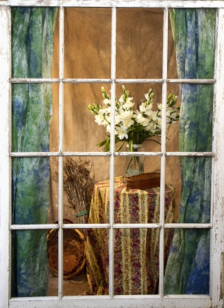 window curtains: Tall white flowers on table looking from outside in through old weathered and worn window pane Stock Photo