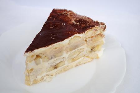 sprinkled: Banana sour cream cake sprinkled with cocoa Stock Photo