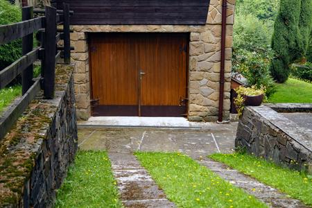 garage doors: Driveway to wooden garage doors with grass
