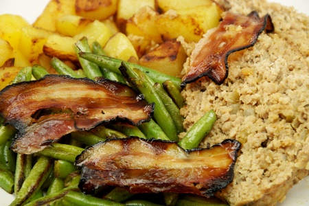 albondigas: meatloaf with potatoes bacon and green beans served on white plate Foto de archivo