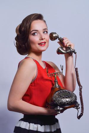 Beautiful girl talking on retro telephone pin-up style