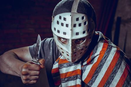 maniac: Portrait of Maniac with knife in dark basement. Stock Photo