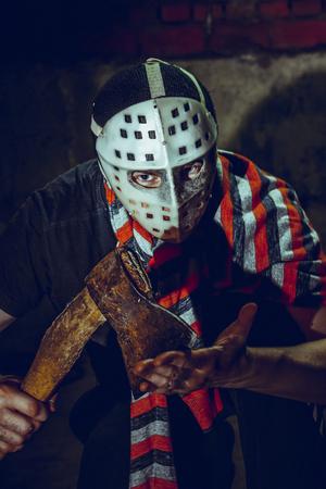 maniac: Portrait of Maniac with axe in dark basement.