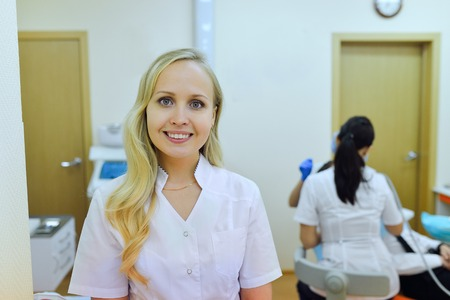 stomatology: medicine, stomatology and healthcare concept - happy female dentist in white coat at dental clinic office