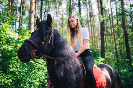 Yong girl in the Woods ride on black horse. Imagens
