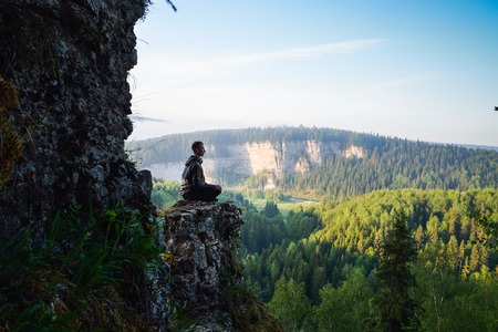 Man sitting on the top of the mountain in yoga pose, leisure in harmony with nature.