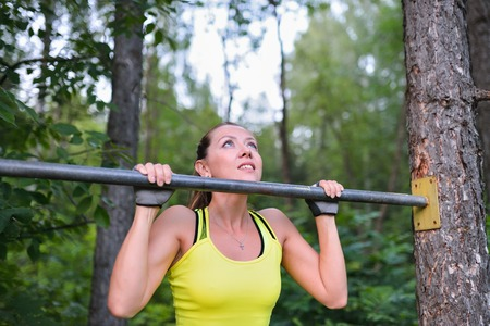 gripping bars: Fit woman training pull ups on horizontal bar in city park outdoors.