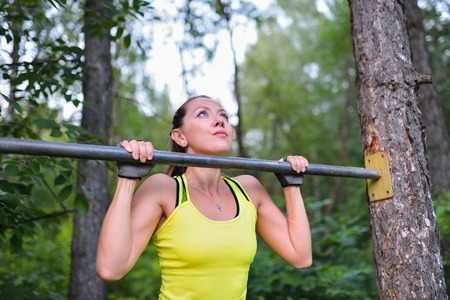 hang body: Fit woman training pull ups on horizontal bar in city park outdoors.