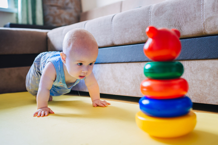 trial indoor: Cute little kid trying to get to the toy. Stock Photo