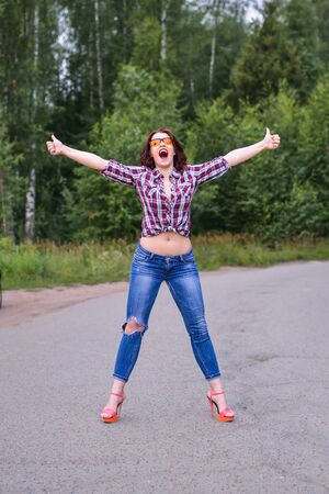 hitched: Young woman persistently hitchhiking gesture at countryside.