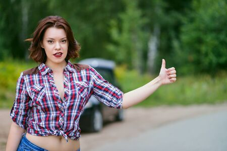 hitched: Beautiful young woman hitchhiking gesture at countryside, broken car at background.
