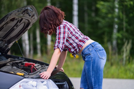 beautiful young woman repairing herbroken car near the road.