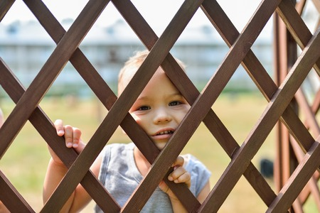 punishing: Sad and lonely child looking out through fence. Children stress and negative emotions
