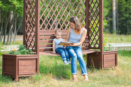 mother on bench: Mother and son sitting on a bench in a park and reading a book.
