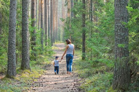walk in: Mother and baby walk on country rural road in pine forest. Stock Photo