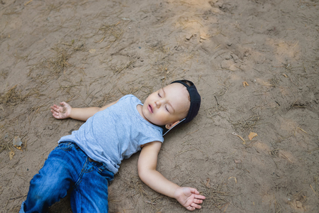 Little boy laying on ground pretending sleep or unconscious. Standard-Bild