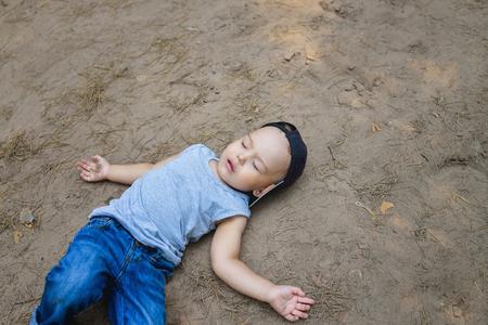 Little boy laying on ground pretending sleep or unconscious. Archivio Fotografico