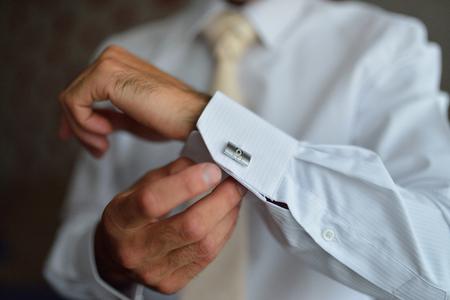 cufflink: close up of a hand man how wears white shirt and cufflink.