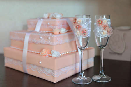 fancy box: Two fancy wedding glasses with decorated box on background. Carrot color Stock Photo