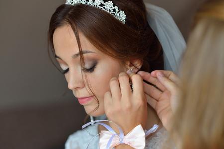 Novia morena hermosa elegante en el vestido blanco y su amigo que ayudan con preparaciones de la boda.
