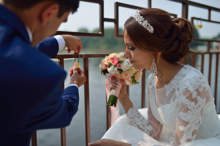Bride and groom makingt the tradition at weddings hanging the lock on the bridge. Stock Photo