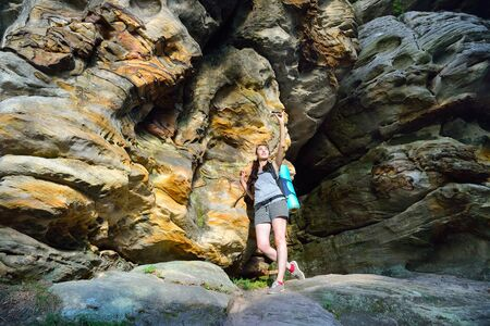 intresting: Woman Hiker with backpack exploring beautiful colorful canyon, and making photo on smartphone .