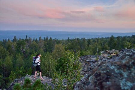 Lady hiker with backpack moving to top of the mountain at sunset.