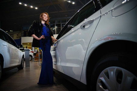 manteau de fourrure: Elegant woman with red hair in blue dress and fur coat standing near new modern car.