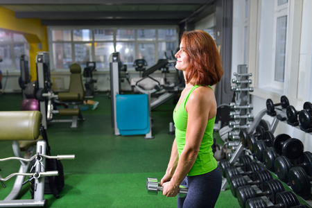 waistline: fitness, sport, training and lifestyle concept - middle aged woman doing exercises with dumbbells at gym .