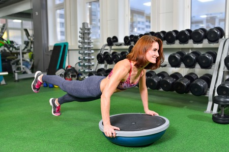 planking: Fitness woman planking doing the body weight exercise for core strength training in gym with bosu balance trainer.