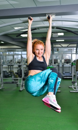 Fitness, sport, exercising lifestyle - Fit woman doing exercises on horizontal bar in gym.